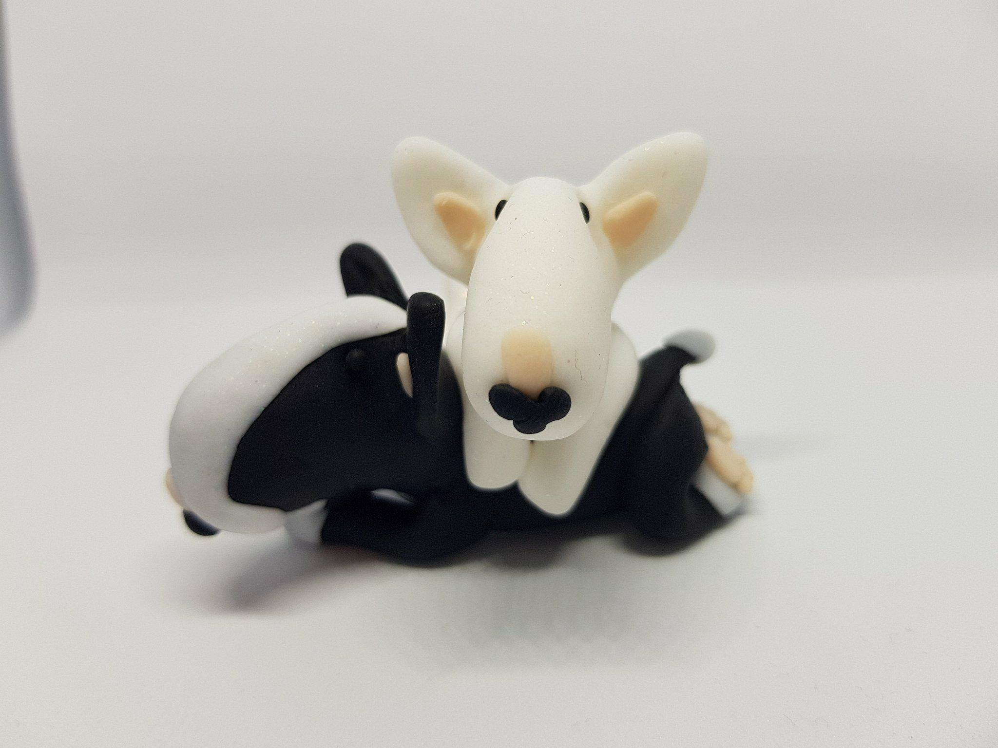 A black english bull terrier figure with another white english bull terrier laying over it