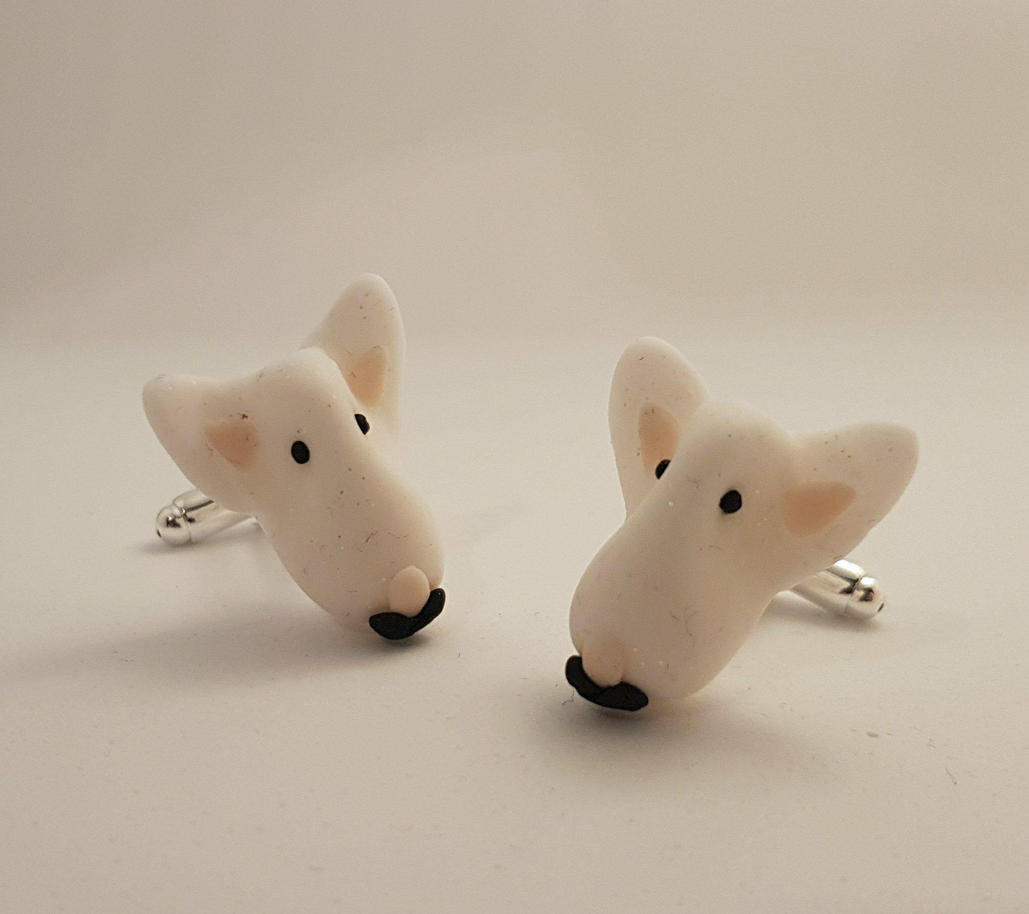 A pair of white english bull terrier faces attached to cuff links