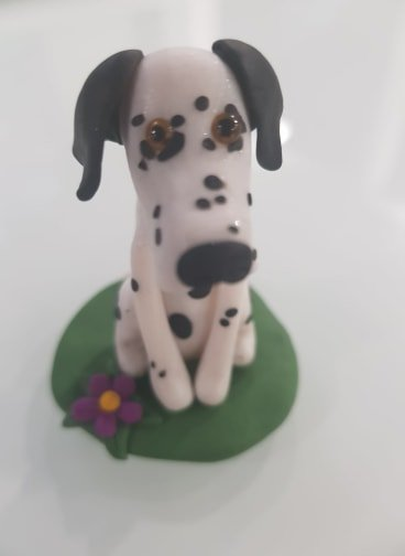 A dalmatian figure sitting on a green base. Front facing