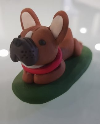 A figure of a french bull dog laying down on a green base. Front facing