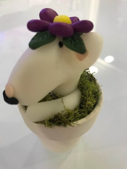 A face and legs of an english bull terrier peeking out of a flower pot with a flower on its head