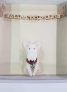 A white box frame with an english bull terrier figure inside. Above is a clothes line with pegs and personalised letter beads