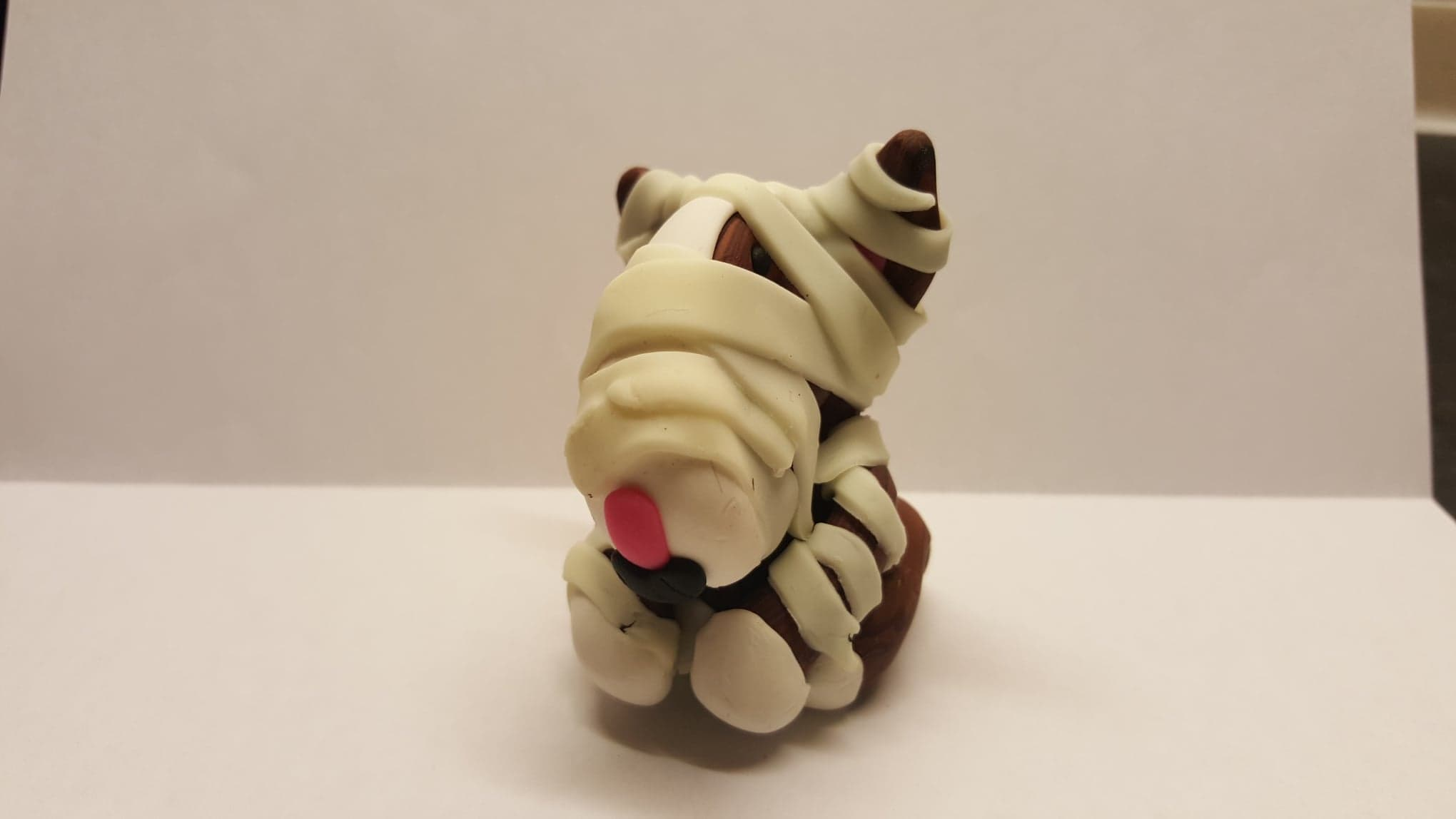 An english bull terrier figure with green glow in the dark bandages under normal light wrapped in the style of a mummy