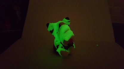 An english bull terrier figure with green glow in the dark bandages wrapped in the style of a mummy