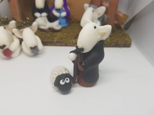 An english bull terrier figure in the style of a shepherd along with a sheep figure for the nativity set