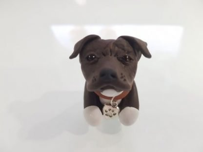 A figure of a brindle staffordshire bull terrier (staffie) front facing