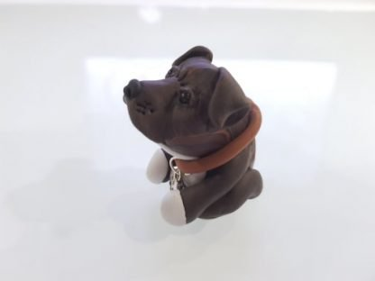 A figure of a brindle staffordshire bull terrier (staffie). Left side facing