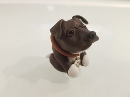 A figure of a brindle staffordshire bull terrier (staffie) right side facing