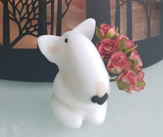 A white english bull terrier figure holding a bunch of flowers