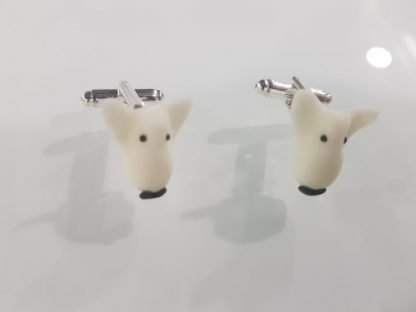 A pair of glow in the dark cuff links in normal light with an english bull terrier face