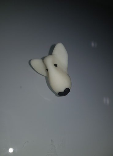 A pin badge of a white english bull terrier face